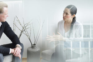 Man och kvinna sitter i konferensrum och diskuterar