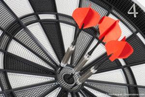 three red darts hit the bull's eye
